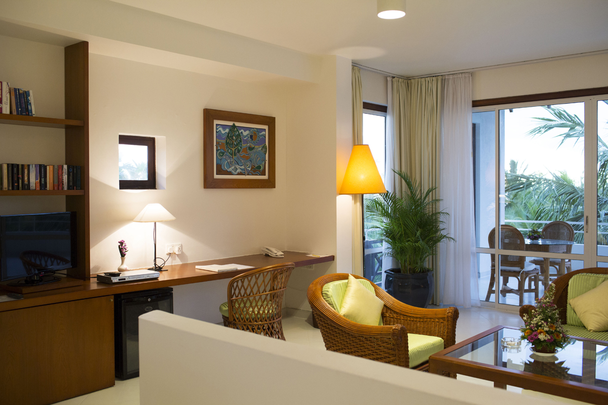 Hotelzimmerwohnbereich mit Schrebitisch, Schrank und Stühlen