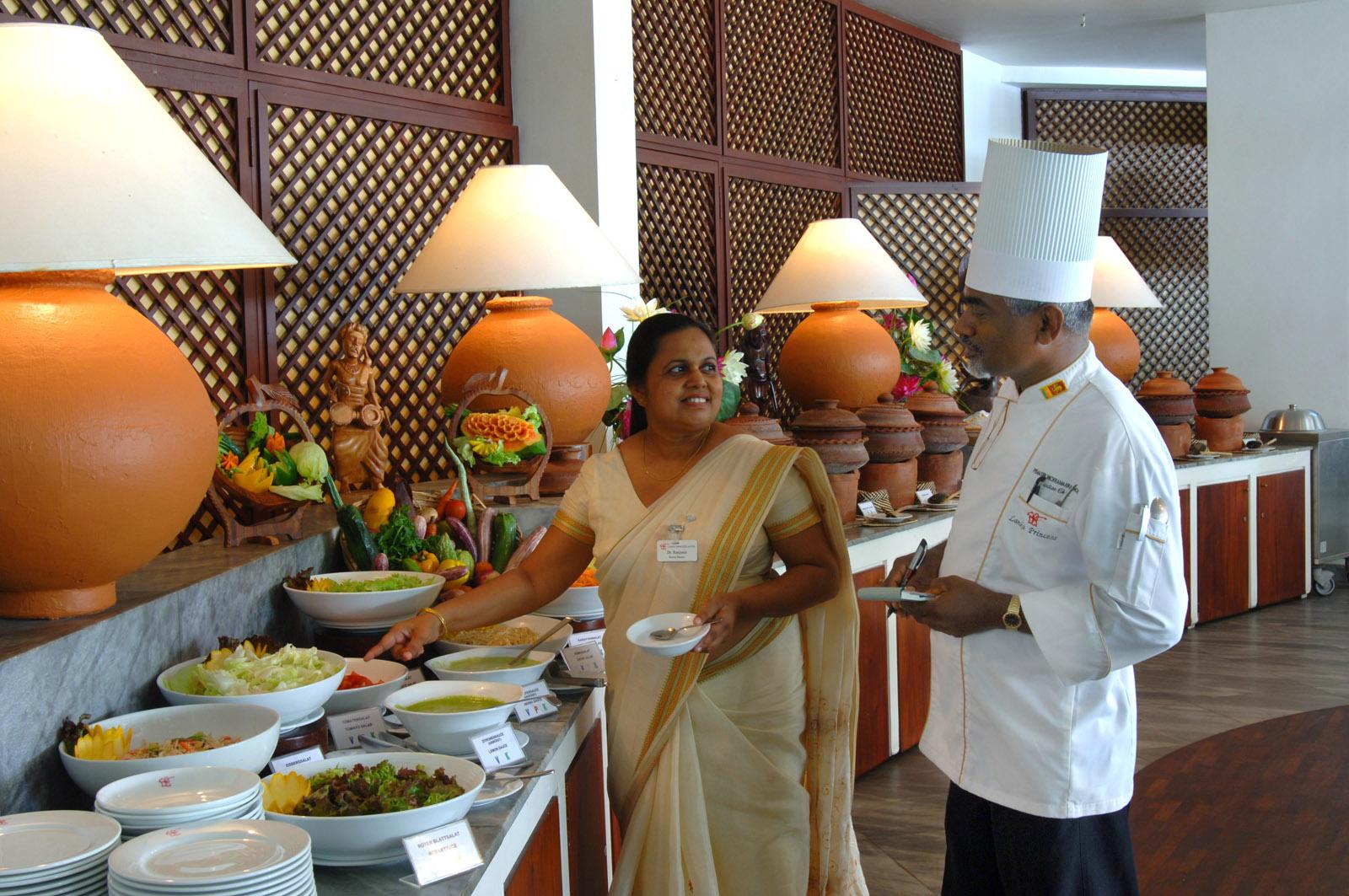 Koch und Angestelle vor dem Buffet im Hotel