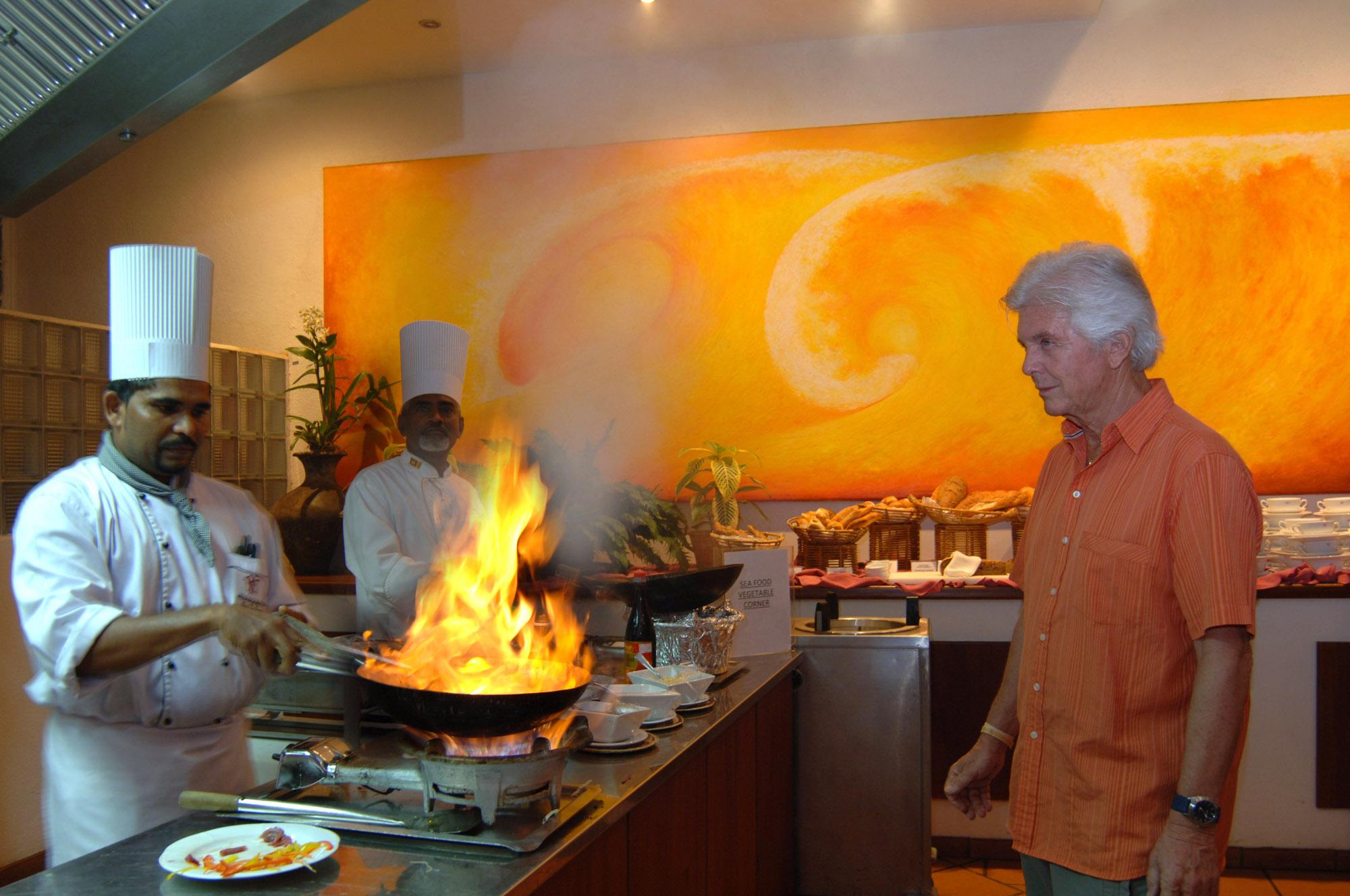 Koch an offener Flamme mit Gast