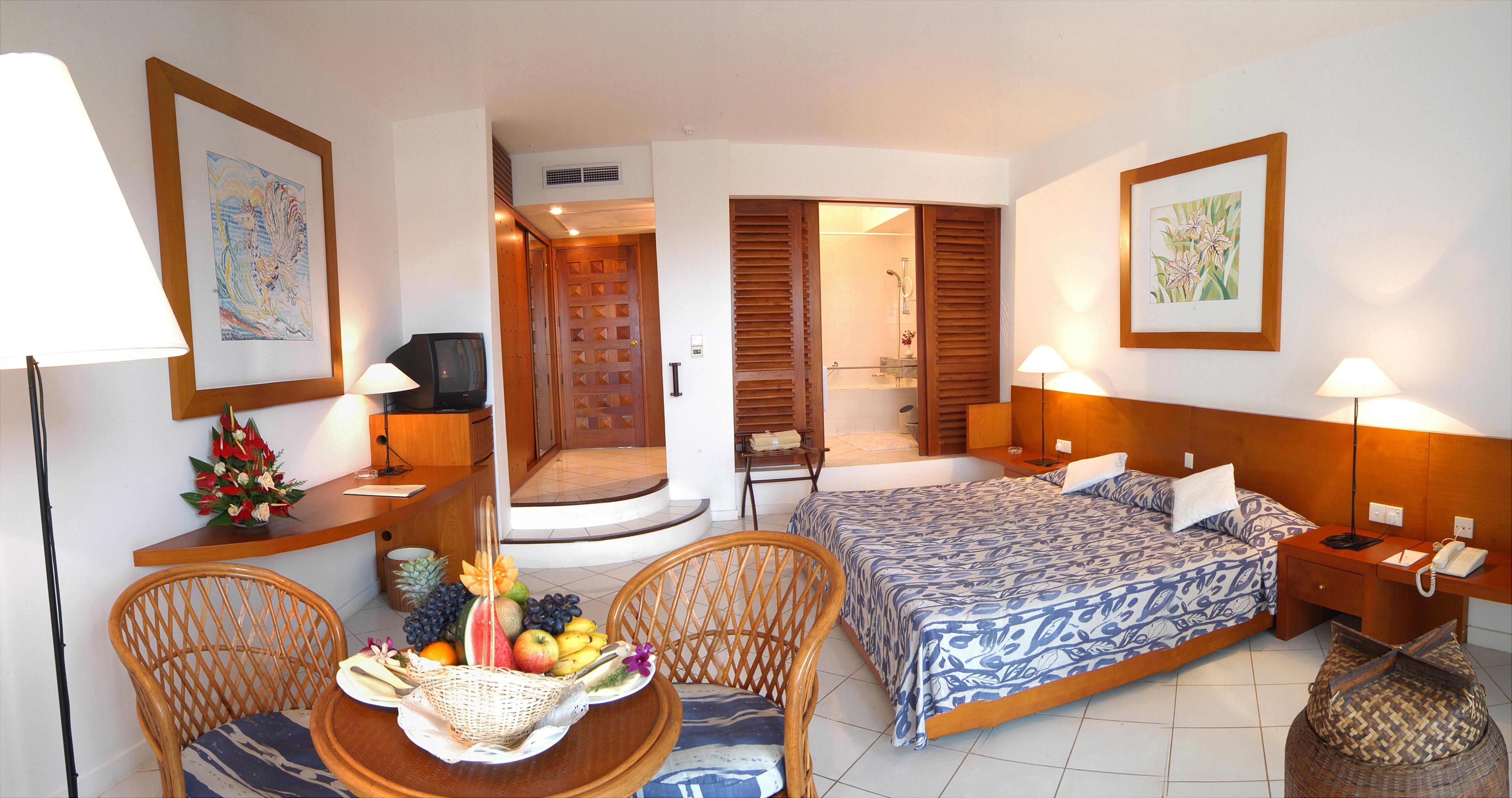 Comfort Zimmer mit blauer Bettwäsche und teilweise Holzmöbel