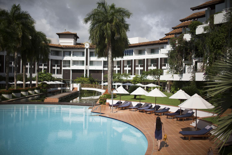 Hotel Pool mit Liegen und einer Frau in blau