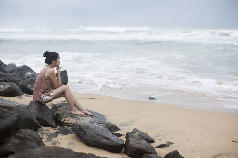 Frau auf Steinen sitzend am Meer Kinn auf Hand abstützend